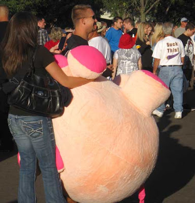 Woman holding a gigantic, pink round stuffed animal pig. Nearby a man wears a shirt that says Suck on this, which has an arrow pointing at the pig