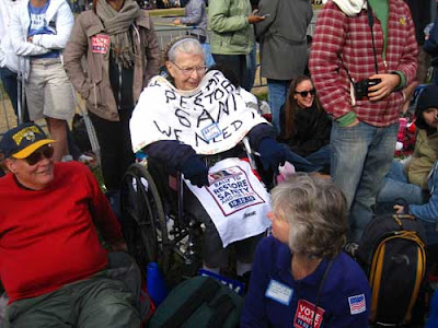 Elderly woman in wheelchair surrounded by other people over 50