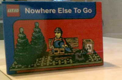 Solitary Lego bestubbled figure on a bench beside two pine trees, sack of belongings, trash can titled Nowhere Else to Go