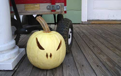 A yellow pumpkin cut as a jack-o-lantern on a porch