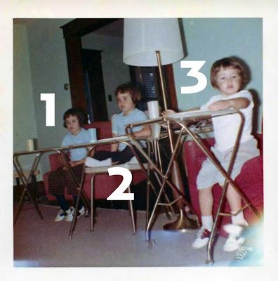 Snapshot of three dark-haired little girls sitting behind t.v. trays