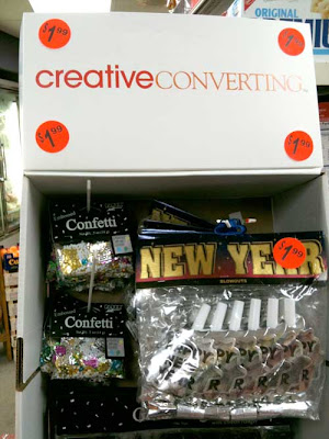 Photo of a white cardboard point-of-purchase display holding New Year's Eve decorations. The top of the display reads CreativeConverting