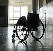Imagen de una silla de ruedas sin nadie en el ella, en medio de un pasillo solitaria