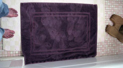 two pairs of feet, one real, one wood, and wet footprints on a purple bathmat