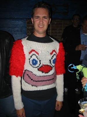 Wil Wheaton frowning while wearing a horrible red and white clown sweater
