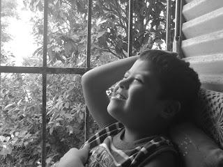 """Uma foto em preto e branco, de um menino com síndrome de down, com uma janela ao fundo, por onde entra uma luz que ilumina seu rosto e seu sorriso, com o título """"disfruto de la vida"""", de autoria de Gladis Suzana, Mendonza, Argentina. Esta foto foi premiada por sua representação da capacidade de pessoas com deficiência de também desfrutarem do direito à vida, com descontração, alegria e suavidade."""