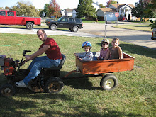 Kids going for a ride on our neighbor Ricks Lawn mower!