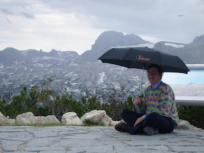 Jim sitting with an ICCHP umbrella, mountains in the background