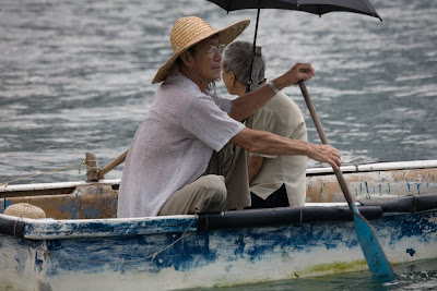 Old man and wife in a rowboat with umbrella