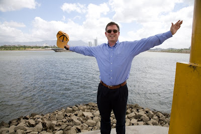 Jim Fruchterman with arms spread wide by a river