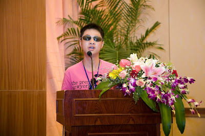 Student with dark glasses at podium with flowers