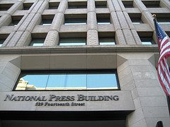 Looking up at the national press club sign on building, with American flag, courtesy of eszter