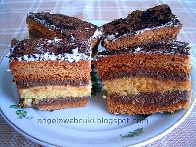 Csokikrémes mézes sütemény, mézes lappal, vaníliás piskótával, grízes csokoládé krémmel, vékonyan tojásfehérjehabbal lekenve és kakaóporral megszórva.