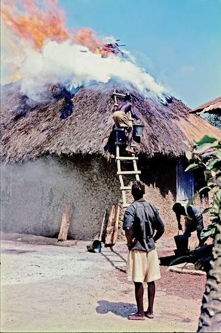 thatch roof on fire in village on the road to Panguma