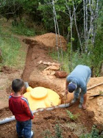 Horacio oversees the final connections on the new septic system