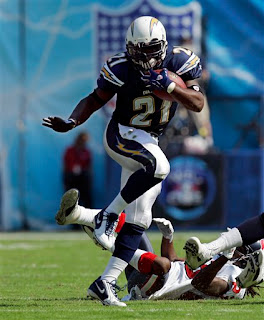 LaDanian Tomlinson does a near perfect Heisman pose while carrying the ball against the Texans