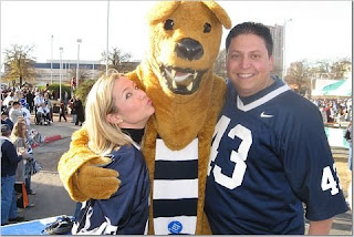 the only two educated people at a Penn State game pose for a picture with --- Freedo