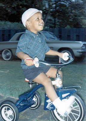 Photo of young Barack Obama, playing on his tricycle.
