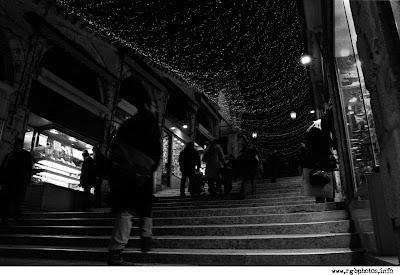 Fotografia notturna in bianco e nero a Venezia: un passante cammina per una calle addobbata a festa