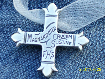 sheer white ribbon with silver Daughters of the King cross laying on blue denim background - writing on cross says in Latin, ''Magnanimiter Crucem Sustine,'' the watchword of the Order, meaning ''With heart, mind and spirit uphold and bear the cross.''  At the base of the cross are the letters ''FHS,'' initials that stand for the Motto of the Order:
