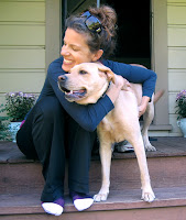Photo of Denise hugging yellow Lab Crumpet on their front porch at home