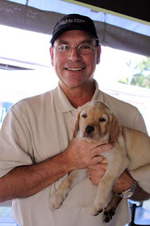 Puppy raiser Brion Hart with a yellow Lab pup