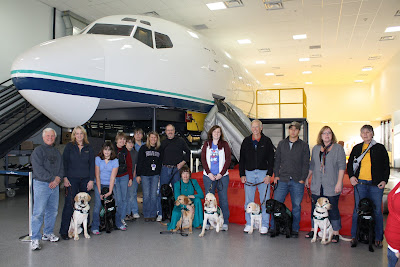 The Eager Eye puppy raising club in front of Alaska Airline's mock-up training aircraft