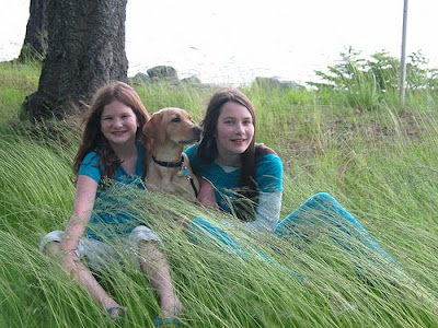 Two young girls, Jenna and Bethany, along with yellow lab Spritz, enjoying the tall grass.