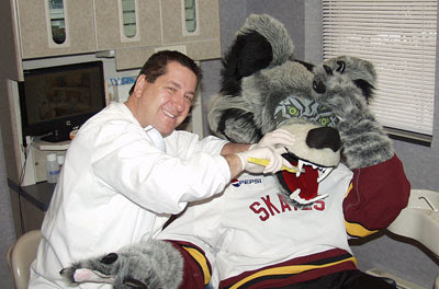 Chicago Wolves mascot, Skate, visits Dr. Mark Humenik, a Chicago Dental Society member.
