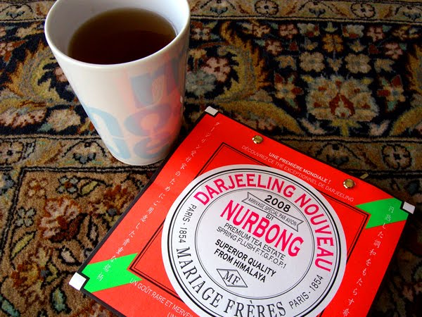 Cup of tea with a package of Darjeeling tea leaves on a kilim.