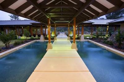 Pasillo exterior entre piscinas en la casa resort