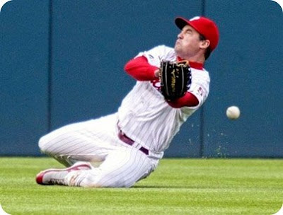 Pat Burrell seems to be having some difficulty fielding this grounder.