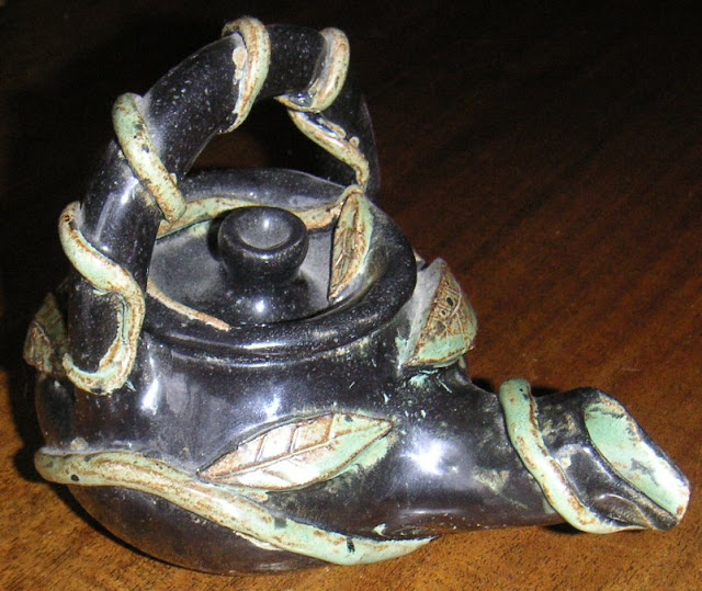 handmade tea pot decorated with leaves and vines