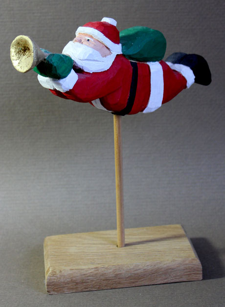 carved flying wooden Santa blowing a horn