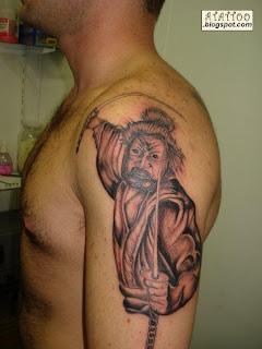 Samurai preto e cinza tatuado no braço.