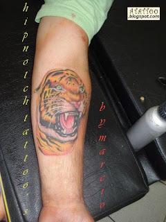 Tigre tatuado no ante-braço.