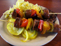 Click to enlarge - Sausage brochette on a bed of yellow squash and noodles