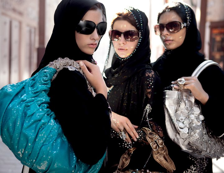 three women in black abayas with sunglasses and large purses