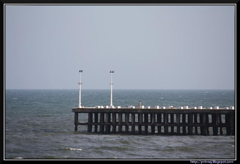 A lone man on a pier