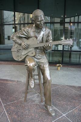 Estátua de bronze no foyer de entrada do Bank of America, na 4ª Avenida Norte, 315, Nashville, Tennessee. Crédito: http://www.lordscapes.com/misterguitar.html