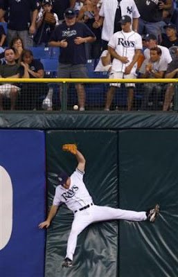 Tampa Bay Rays' Gabe Gross falls while trying catch a triple by New York Yankees' Robinson Cano