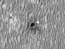 This image shows NASA's Mars Exploration Rover Opportunity perched on the edge of