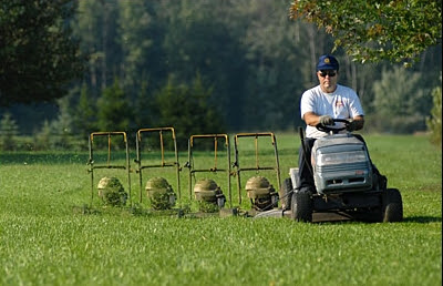 Man operating 5 mowers simultaneously