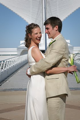 Ellie laughing as John hugs her in front of the Calatrava before their June wedding