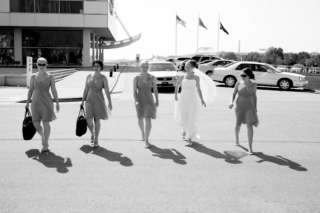 Black and White candid of Bride and bridesmaids walking by Discovery World before wedding