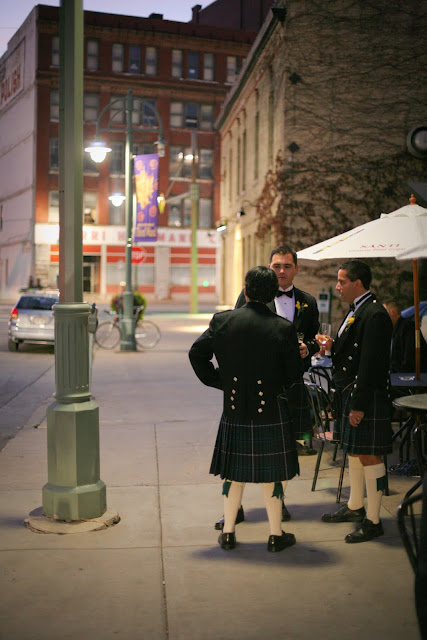 Three groomsmen in kilts relax outside Hinterland Erie Street Gastropub wedding recption