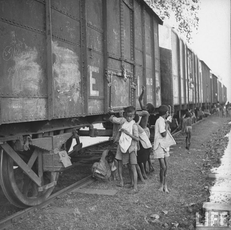 Children poking grain cars with wires, trying to pierce bags and pull grain down into bags