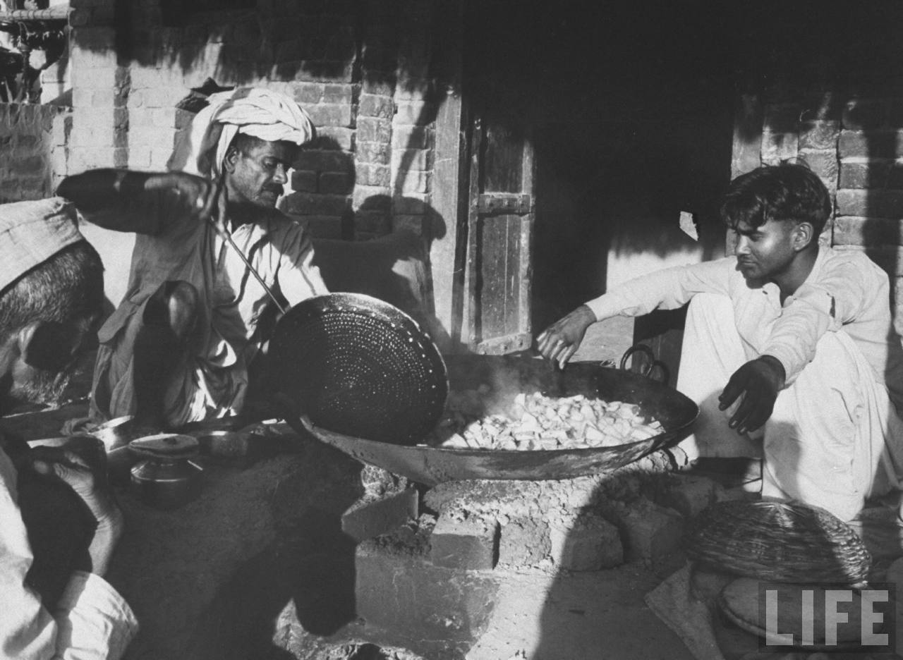 Men cooking food in a village - 1962