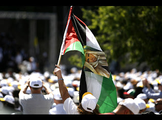 People and pilgrims celebrating the arrival of Pope Benedict XVI, a man with Palestinian flag picture