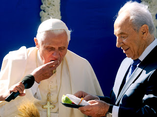 Pope Benedict XVI eating a date in the welcoming ceremony at the presidential residence in Jerusalem photo